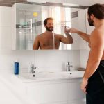 man-in-his-bathroom-selecting-a-music-on-his-smart-What-Is-a-Smart-Mirror